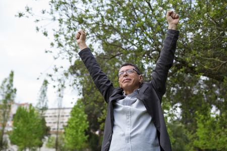 Cheerful middle-aged man raising arms in park. Guy wearing casual clothes and celebrating success with green trees in background. Achievement and nature concept. Front view.