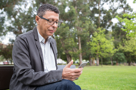 Content man using smartphone and sitting on bench in park. Guy wearing casual clothes and texting on gadget with green lawn and trees in background. Communication and nature concept. Stockfoto