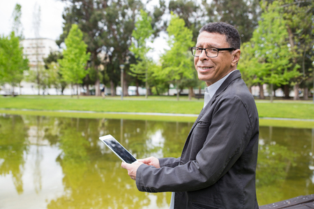 Happy man using tablet and standing in city park. Guy wearing casual clothes and holding gadget with pond and green trees in background. Communication and nature concept. Side view. Stockfoto