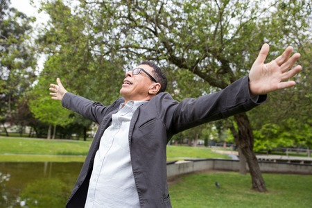 Cheerful middle-aged man spreading hands in park. Guy wearing casual clothes and celebrating success with green trees and lawn in background. Win and nature concept.