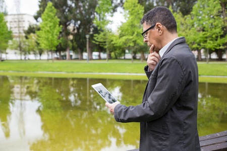 Pensive man using tablet and standing in city park. Guy wearing casual clothes, touching chin and holding gadget with pond and green trees in background. Communication and nature concept. Side view.