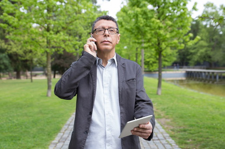 Pensive man using tablet and talking on phone in park. Guy wearing casual clothes and walking on stone pavement with green trees in background. Communication and nature concept. Front view.