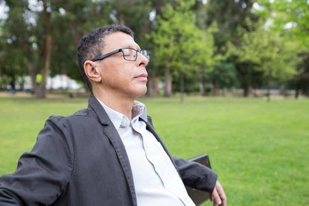 Relaxed middle-aged man sitting on bench in park. Guy wearing casual clothes and keeping his eyes closed with green lawn and trees in background. Relaxation and nature concept. Stockfoto