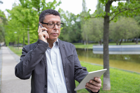 Serious man browsing on tablet and talking on phone in park. Guy wearing casual clothes and walking on pavement with green trees in background. Communication and nature concept. Front view.