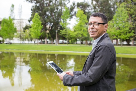 Smiling man using tablet and standing in city park. Guy wearing casual clothes and holding gadget with pond and green trees in background. Communication and nature concept. Side view.