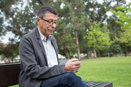 Focused man using smartphone and sitting on bench in park. Guy wearing casual clothes and browsing on gadget with green lawn and trees in background. Communication and nature concept. Stockfoto