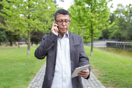 Focused man using tablet and talking on phone in park. Guy wearing casual clothes and walking on stone pavement with green trees in background. Communication and nature concept. Front view.