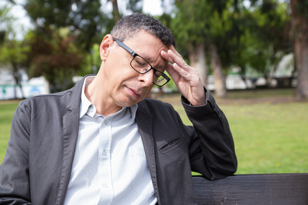 Tired middle-aged man touching head and sitting on bench in park. Guy wearing casual clothes, frowning and keeping his eyes closed with lawn and trees in background. Overwork concept. Front view.
