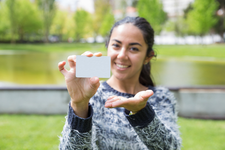 Happy young woman showing blank business card in city park. Pretty lady wearing sweater and standing with blurred green view in background. Introduction concept. Front view.