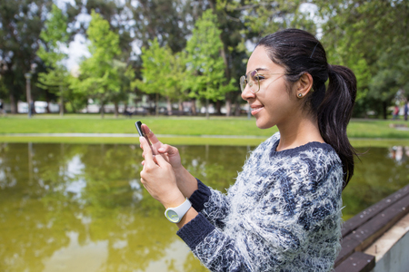 Smiling young woman using smartphone in park. Pretty lady wearing sweater and standing with pond and green trees in background. Communication and nature concept. Side view.