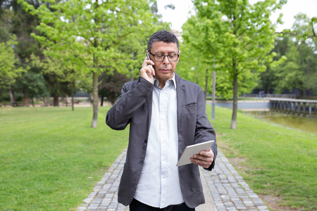 Serious man using tablet and talking on phone in park. Guy wearing casual clothes and walking on stone pavement with green trees in background. Communication and nature concept. Front view.