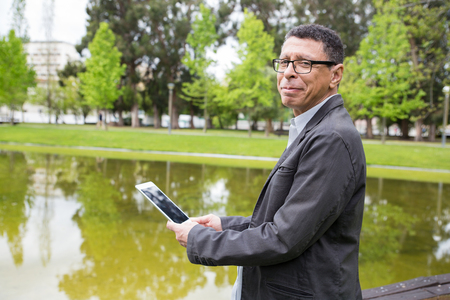 Positive man using tablet and standing in city park. Guy wearing casual clothes and holding gadget with pond and green trees in background. Communication and nature concept. Side view.