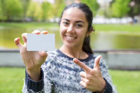 Smiling woman pointing at blank business card in city park. Blurred pretty young lady wearing sweater and standing with pond and green trees in background. Introduction concept. Front view.