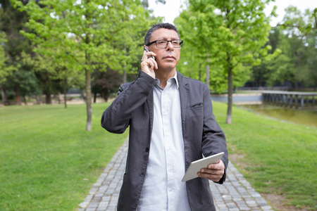 Pensive man using tablet and calling on phone in park. Guy wearing casual clothes and walking on stone pavement with green trees in background. Communication and nature concept. Front view.