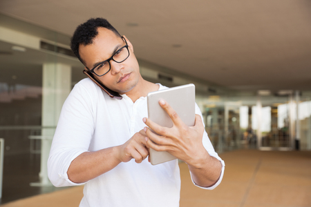 Medium shot of serious young mixed-race man in spectacles and white T-shirt standing at office building, working on tablet, talking on phone, looking at camera. Front view. Lifestyle concept