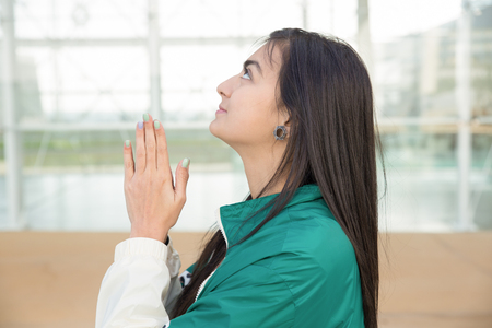 Positive girl thanking God for help or luck. Side view of young woman putting hands together in pray and looking up. Pray concept
