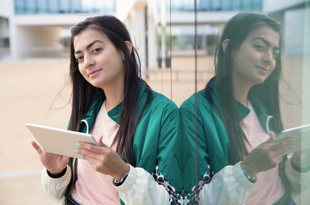Positive Latin girl using tablet outdoors. Young woman in casual leaning on glass wall, holding gadget and looking at camera. Communication concept