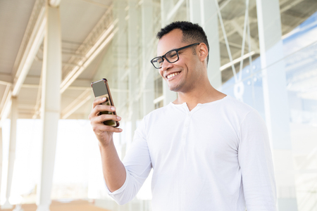 Bottom view of smiling young mixed-race man in spectacles and white T-shirt standing at office building, holding phone in hands, looking aside. Lifestyle concept