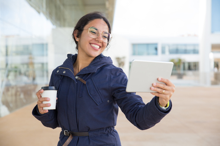 Happy excited girl enjoying coffee and video call outdoors. Young woman in overcoat and eyeglasses holding takeaway cup and smiling at tablet screen. Outdoor coffee break concept