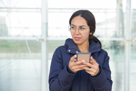Pensive beautiful girl surfing internet on phone outdoors. Young woman in overcoat and eyeglasses standing at glass wall, holding smartphone and looking away. Mobile internet concept
