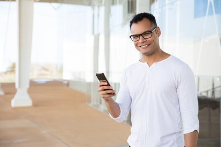 Medium shot of smiling young mixed-race man in spectacles and white T-shirt standing at office building, holding phone in hands, turning head to camera, looking. Lifestyle concept Stockfoto