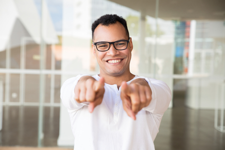 Medium shot of smiling young mixed-race man in spectacles and white T-shirt standing at office building, looking straight at camera, pointing at the camera with both hands. Lifestyle concept