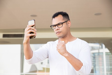 Bottom view of serious young mixed-race man in spectacles and white T-shirt finishing phone call, receiving good news, celebrating success. Lifestyle, work concept