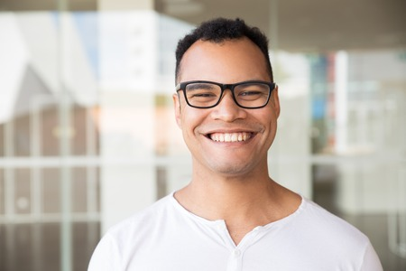 Medium shot of smiling young mixed-race man in spectacles and white T-shirt standing at office building, looking straight at camera. Lifestyle concept