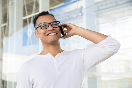 Bottom view of smiling young mixed-race man in spectacles and white T-shirt standing at office building, talking on phone. Lifestyle concept