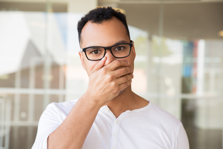 Medium shot of surprised young mixed-race man in spectacles and white T-shirt standing at office building, looking straight at camera, closing mouth with hand, looking shocked. Lifestyle concept Stockfoto