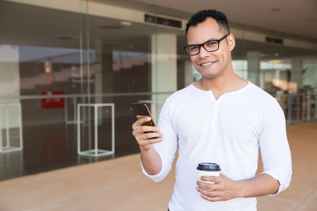 Medium shot of smiling young mixed-race man in spectacles and white T-shirt standing at office building, texting on phone, holding takeaway coffee, looking at camera. Front view. Lifestyle concept