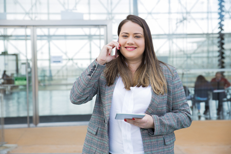 Smiling business woman calling on smartphone outdoors. Lady standing and holding tablet computer with building glass wall in background. Business and technology concept. Front view. Stockfoto - 123136039