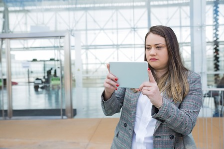Serious inspector working on site. Young woman in formal jacket standing in modern business space and using tablet for shooting or checking. Inspection concept