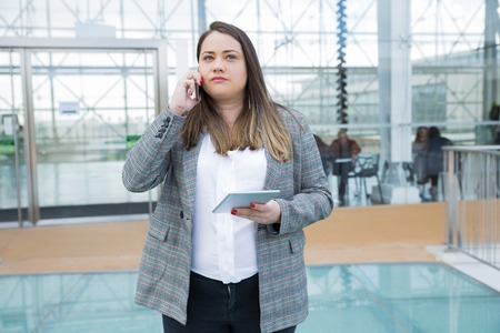 Serious manager talking on phone in modern office lobby. Young woman in formal jacket standing against glass wall, holding tablet and speaking on cell. Communication concept Stockfoto - 123137123