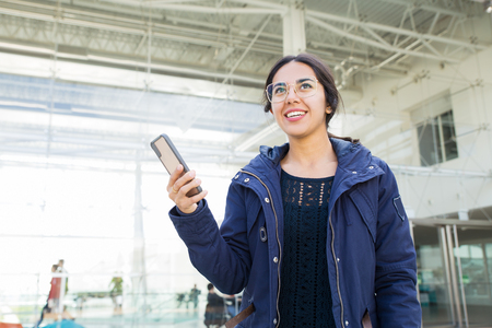 Smiling positive girl using phone outdoors. Young woman in overcoat standing against building glass wall, holding smartphone and looking away. Mobile communication concept Stockfoto - 123137124