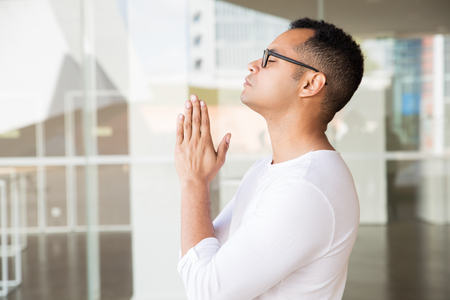Side view of serious young mixed-race man with closed eyes in white T-shirt, putting hands in praying position. Lifestyle, religion concept