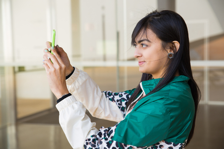 Side view of pretty young mixed-race woman in green jacket making photo on phone. Lifestyle concept