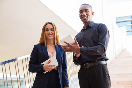 Business people posing and holding tablet computers on stairs. Business man and woman looking at camera and standing with stairway in background. Business and communication concept. Front view.
