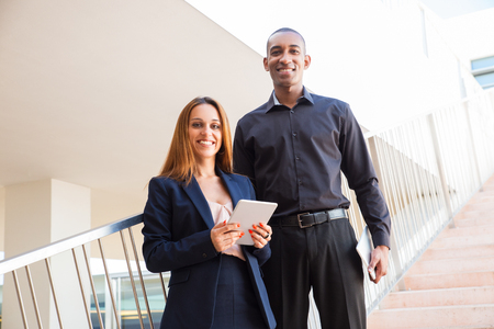 Partners posing and holding tablet computers on stairs. Business man and woman looking at camera and standing with railing and stairway in background. Technology and business concept. Front view.