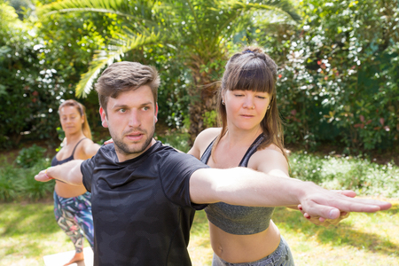 Fokussierter Yogalehrer, der Neulingen hilft, mit der Kriegerpose fertig zu werden. Mann macht Yoga im Freien, Frau passt seine Hände an. Trainings-Yoga-Konzept Standard-Bild