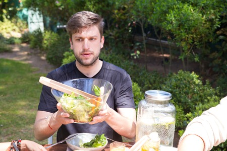 Portrait of serious young man passing salad at lunch outdoors. Guy having meal with family outside. Brunch concept Standard-Bild