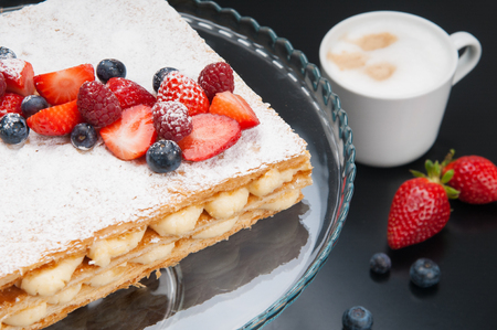 Close-up of appetizing Napoleon cake with berry and sweet powder. Cappuccino in cup and cake stand with decorated cake on table. Breakfast in coffee shop concept