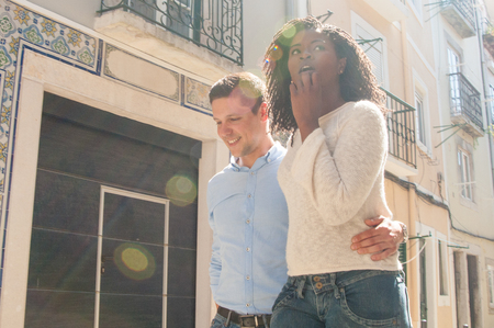 Excited multiethnic couple going sightseeing around city. Happy Caucasian guy embracing impressed Afro American girl, walking through old city and smiling. Travel concept