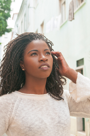 Pensive black girl walking down city alley. Outdoor portrait of young beautiful young woman in casual with dreads looking up. Female portrait concept