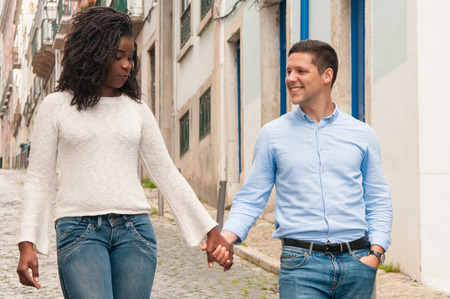 Sweet mix raced couple walking down old European alley. African American girl and her Caucasian boyfriend holding hands, walking outdoors, chatting and laughing. Sweet millennial couple concept Stock Photo - 124757764