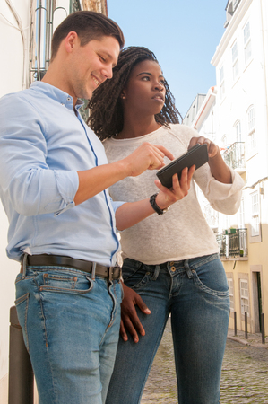 Mix raced couple of tourist consulting navigation app. Young Caucasian man and Afro American woman standing in city alley and using gadget. Navigation and tourism concept