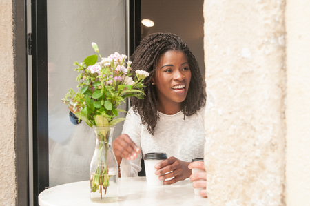 Positive black girl excited with discussion. Beautiful young woman in casual with dreads drinking coffee in cafe, smiling and talking to partner. Coffee break concept Banco de Imagens