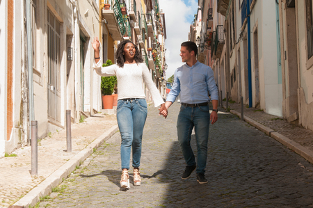 Positive cheerful multiethnic couple dating outdoors and chatting. African American girl and Caucasian guy holding hands and walking down old alley. Dating outdoors concept