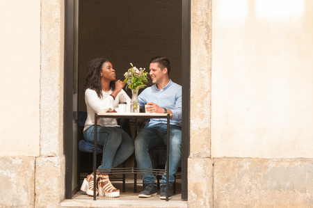 Positive handsome Caucasian guy dating beautiful Afro American girl. Happy interracial couple sitting at table in doorway and drinking coffee. Romantic date concept Stock Photo