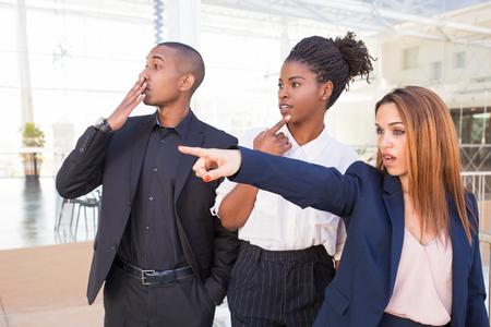 Überraschte Büroangestellte, die eine schockierende Szene beobachten. Drei aufgeregte Geschäftsleute, die mit dem Finger zeigen und wegstarren. Schockkonzept